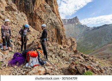 Mountain climbers discussing tactic of ascent. Three people male female talking each other about plan of climb and using gear staying on red rocky terrain high mountain landscape background