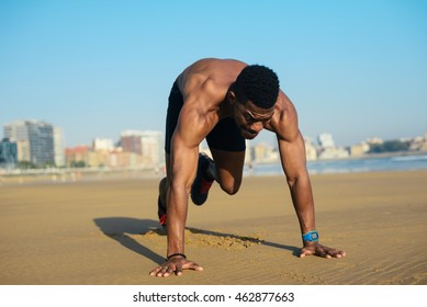 Mountain climbers exercise. Fit man warming up before running at the beach. Black athlete on hiit cardio outdoor workout.