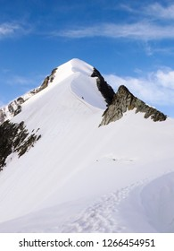 mountain climbers on a steep and narrow snow ridge leading to a high peak in the Swiss Alps