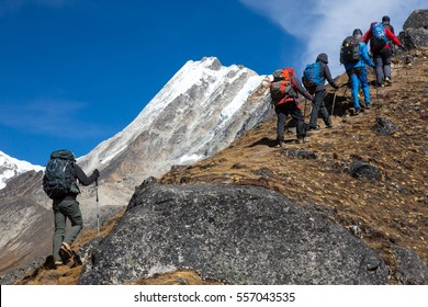 Mountain Climbers Team with Backpacks and walking Poles walking up along rocky Ridge toward high Altitude snowy Peak