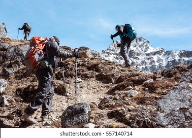 Mountain Climbers Team with Backpacks and walking Poles walking up along rocky Footpath toward high Altitude snowy Peak