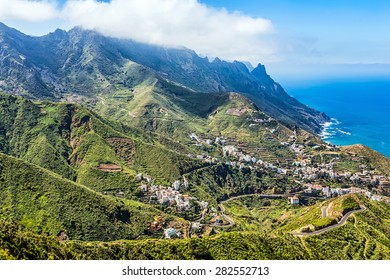 Mountain and clouds with small city or village and sky horizon landscape near the shore of Atlantic ocean in Tenerife Canary island, Spain