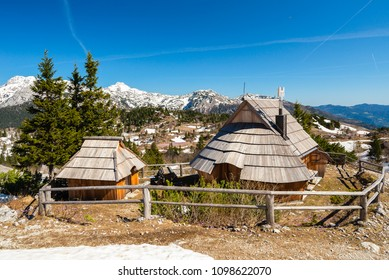 Mountain cottage huts or houses on idyllic hill Velika Planina / Big Pasture Plateau in spring with crocuses in Velika Planina, Slovenia.