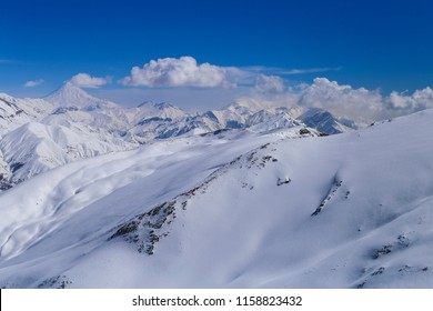 Mountain covered with snow and nature of winter sport resort with the view of damavand peak and shemshak ski resor. north of Tehran iran.