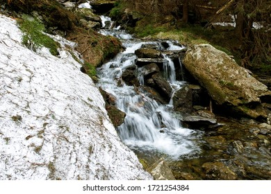 Mountain creek cascading down over stones. Flowing water, motion blur. Waterfall on small river near large snowdrift in forest. Divoky dul, Jeseniky mountains, Czech Republic. - Shutterstock ID 1721254384