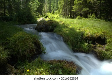 a mountain creek with melting water in the hohe tauern national park in austria, salzburg, at a sunny summer day