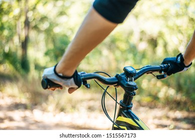 Mountain cyclists grasp the bike handle, focusing on the bicycle neck