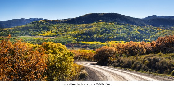Mountain Dirt Road Surrounded by Fall Foliage and Sage Brush. Southern Colorado, San Juan Mountains.