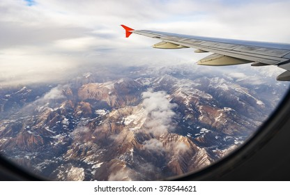 Mountain (Dolomites), clouds and sky as seen through window of an aircraft