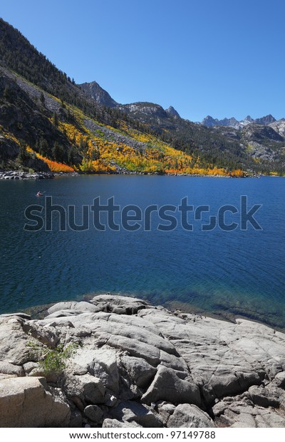 Mountain fishing lake with transparent azure water. Solar autumn midday