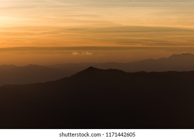 Mountain, fog and yellow gradient sky at dawn