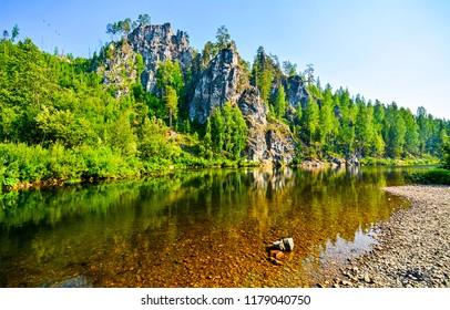 Mountain forest river shore landscape. River water in mountain forest. Forest river in mountains. Mountain forest river landscape