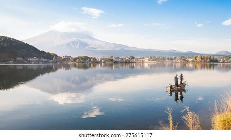 Mountain Fuji and lake kawaguchiko with fisherman on the boat