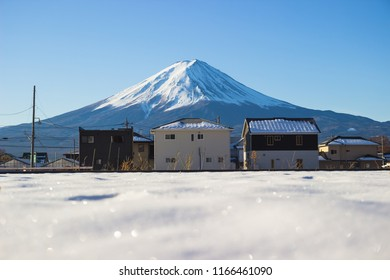 Mountain Fuji with a snow ice cover on the ground with Japanese house village.