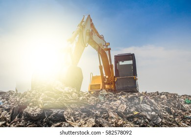 mountain of garbage with working backhoe.