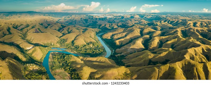 Mountain green hills panorama with curvy river, Merdeka Hill, Bukit Wairinding, East Sumba, Indonesia. Travel Background. Nature landscape. Untouched wild island. Vintage yellow toning
