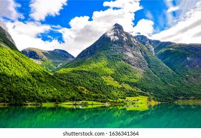 Mountain green lake landscape. Green lake in mountains. Mountain lake view. Mountain lake village
