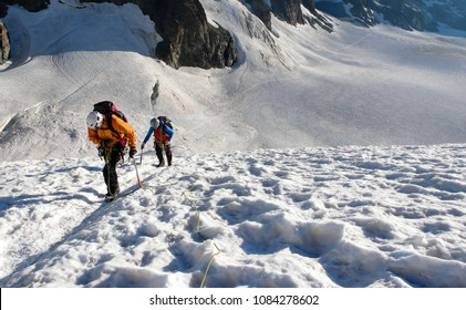 mountain guide and client heading up a glacier towards a high alpine summit on a beautiful summer morning