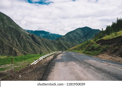 Mountain highway across pass. Asphalt road near mountainside. Amazing colorful highland landscape of majestic nature.
