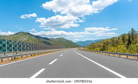 Mountain highway with blue sky and rocky mountains on a background