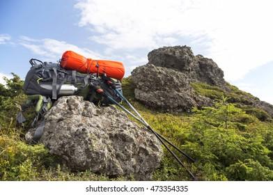 Mountain hiking equipment with backpack, isoprene, trekking sticks on a mountain rock