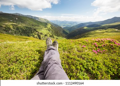 Mountain hiking. Hiker feet resting on top of the hill. Beautiful nature landscape view with Rhododendron flowers