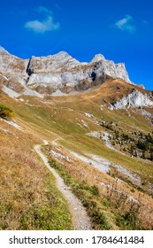 Mountain hiking path in siwss alps with view over impressive summits. Sunny day, clear blue sky. Near Engelberg, SwItzerland.