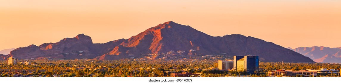 Mountain with homes built into it   At the foot is an urban setting with buildings and Palm trees Phoenix Arizona desert