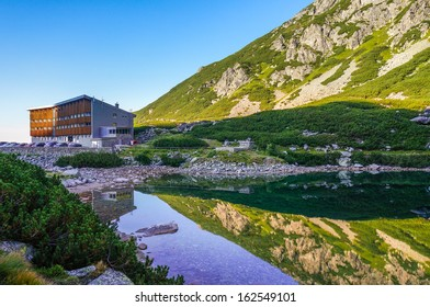 Mountain hotel reflected in the waters of a glacier lake with very clean water. National Park High Tatra (Vysoke Tatry), Slovakia