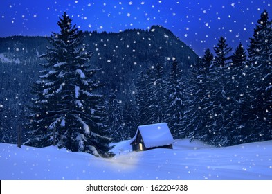 mountain hut in winter with snowflakes at christmas