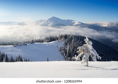 Mountain huts on a snowy hill. Winter landscape on a sunny day