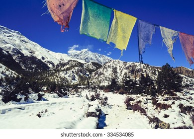 Mountain inspirational landscape in Himalayas, Annapurna range, Nepal. Prayers flag, Mountain ridge with ice and snow over clear blue sunny sky.