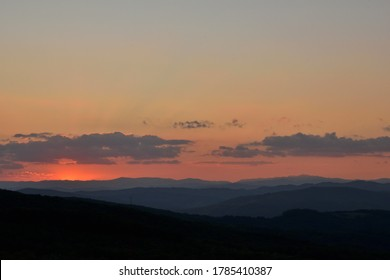 Mountain ladnscape at dawn as the beautiful rosy shades are blending together in harmony, with a few clouds floating above