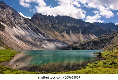 Mountain Lake in the alpine tundra of peaks. Emerald color of pure water comes from a very large depth