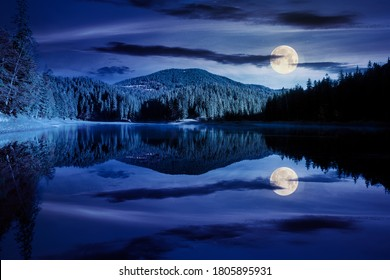 mountain lake among the forest at night. trees in colorful foliage. beautiful landscape in autumn full moon light. clouds and sky reflecting in the water
