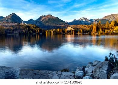 Mountain lake in the autumn season. Beautiful lake in Slovakia - Strbske Pleso. Saturated autumn colors.
