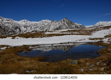 Mountain Lake in front of Snow covered Mountains on Pianaccio, Mortirolo
