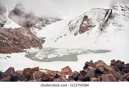 Mountain lake with ice on the snowy mountain Lake of Zaili Alatay in Almaty, Kazakhstan