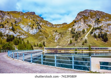 Mountain Lake Lago di Fedaia, Dolomites. Powerful dam blocked the lake. A cool autumn day at Mount Marmolada. The concept of ecological and extreme tourism