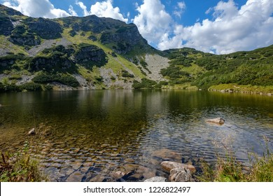 mountain lake panorama view in late summer in Slovakian Carpathian Tatra with reflections of rocky hills in water. Rohacske plesa lakes near Zverovka village.
