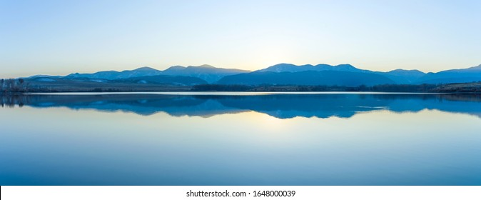 Mountain Lake - A panoramic view of front range mountains reflecting in Bear Creek Lake on a clear Autumn evening. Denver-Lakewood, Colorado, USA.