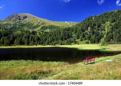 Mountain lake with red bench