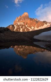Mountain lake with reflection of high rocky peak. Chaukhi, Caucasus, Georgia