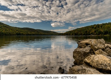 mountain lake with reflection and rocks in the foreground in New England
