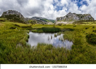 Mountain lake with rocks in the background. Amazing and peaceful scene, fresh green grass covering the ground and blue skies with clouds above. Total silence and peaceful atmosphere. Natural beauty.