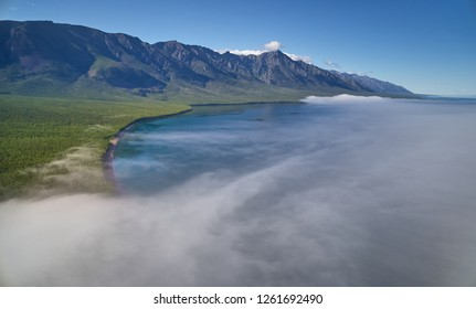 Mountain lake scenery with sun shining to the rocky morning mist above the lake