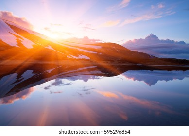 Mountain Lake in the spring. Landscape in the morning. Last snow on the hills. Reflection of the sky in water. Carpathians, Ukraine, Europe