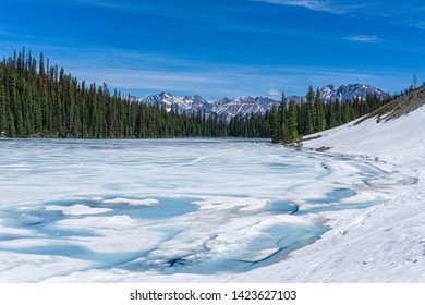 Mountain lake in spring season with melting snow, blue patches of water. Trees, mountains and ble sky ine the background