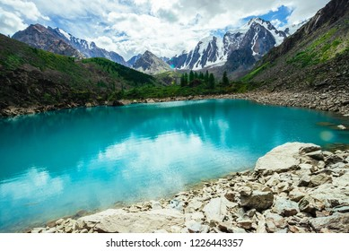 Mountain lake is surrounded by large stones and boulders on front of giant beautiful glacier. Amazing mountain in shape of pyramid. Snowy ridge under cloudy sky. Wonderful atmospheric landscape.