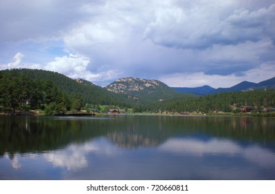 Mountain lake surrounded by pine trees with sky and mountain reflection in water.
